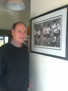 David Sapsted poses beside an atographed framed photo ofth e1962 double team